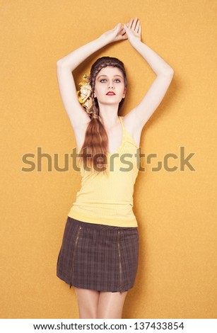 young model with braided hairstyle and a plaid skirt posing on yellow background