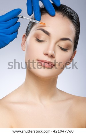 Young model with closed eyes. Head turned aside. Forehead operated by plastic surgeon. Beauty injection by doctor in blue gloves. Beauty portrait, head and shoulders. Indoor, studio - stock photo
