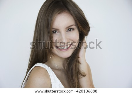 Young model with long hair smiling on a white background