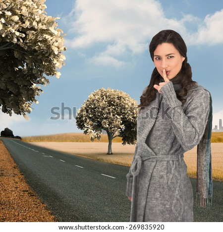 Young model with winter clothes keeping secret against road leading out to the horizon - stock photo