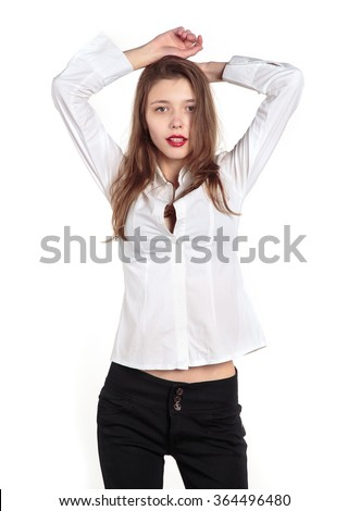Young model woman. Girl in a white shirt blouse on a light background. Woman raised her arms up behind his head. Beautiful woman. Copy space over white light background. - stock photo