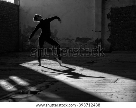 Young modern ballet dancer exercising and dancing in abandoned building.