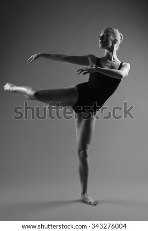 Young modern ballet dancer posing on dark background