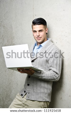 young modern business man with a laptop - stock photo