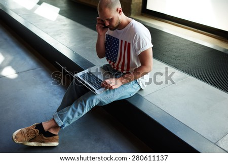 Young modern businessman connecting to wireless on laptop computer while talk on his smart phone, male freelancer working busy on notebook while having conversation on cell phone in loft studio