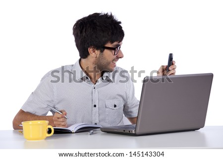 Young modern businessman talking on the phone and working with his laptop - stock photo