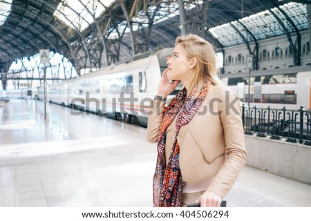 Young modern businesswoman making a business call while waiting for the train at the railway station. attractive young blonde woman using smart-phone while standing on the railway station platform - stock photo