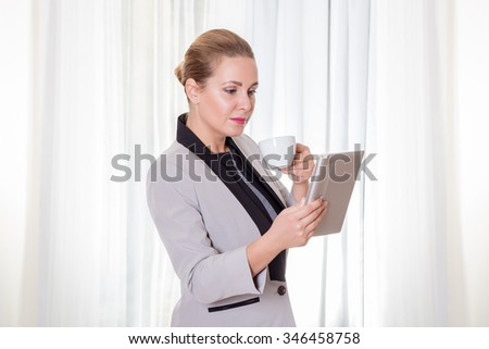 Young modern businesswoman on a coffee break using a tablet computer with white curtain background