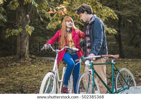 Young modern couple together enjoying romantic walk with bicycle in golden autumn park