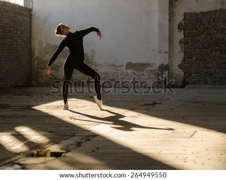 Young modern dancer exercising and dancing in abandoned building. - stock photo