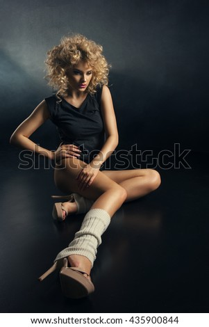 Young modern dancer with blonde curly hair in dark room