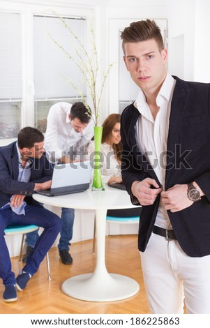 young modern fashion man in a business atmosphere with colleagues behind him