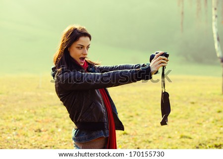 young modern girl in casual clothes take a selfportrait with camera  - stock photo