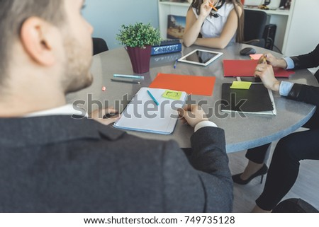 young modern guy and girls are sitting at the office at the table, working together