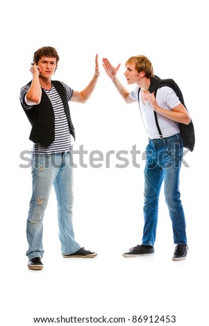 Young modern man with mobile showing wait gesture his indignant friend