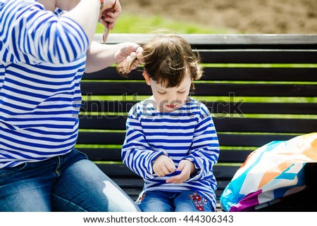 Young modern mother combing her small charming daughter on the bench in the park