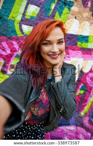 young modern urban girl with red hair in front of graffiti wall making selfie with her phone