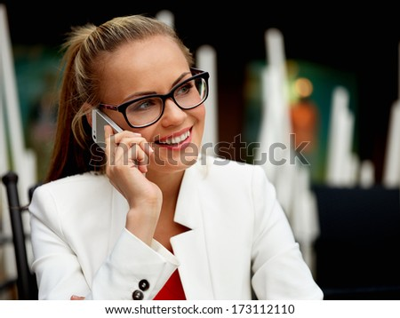 Young modern woman doing smart business via cellular phone