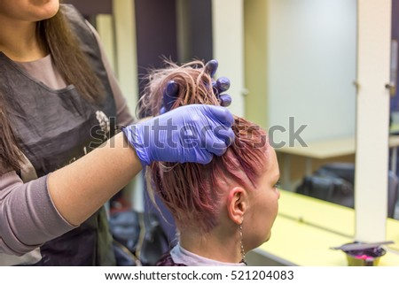 Young modern woman dyeing hair in pink with purple color in barbershop