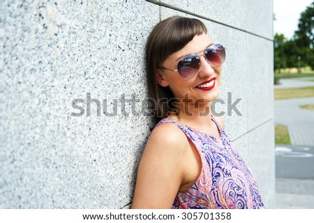 Young modern woman in sunglasses by the wall in city smiling at camera. - stock photo