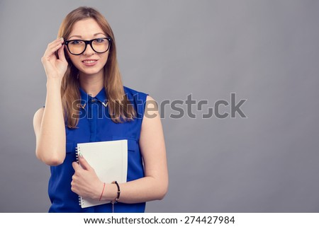 Young modern woman of European appearance holds a notebook to take notes. Woman wearing glasses. Girl student. Near person has space for text. Clever girl american. Education is good. Make report. - stock photo