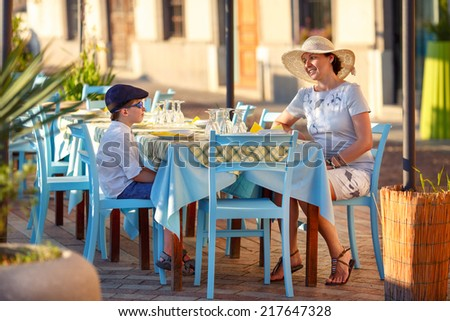 Young mom and her cute little son in street cafe, - stock photo