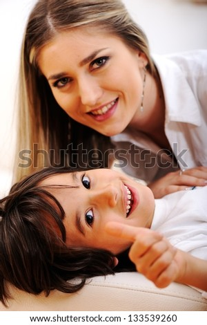 Young mom and her little son together on couch in living room - stock photo
