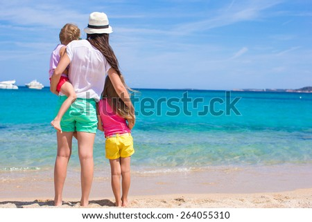 Young mom and little girls at white beach on sunny day