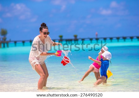 Young mom and little girls having fun during summer beach vacation - stock photo