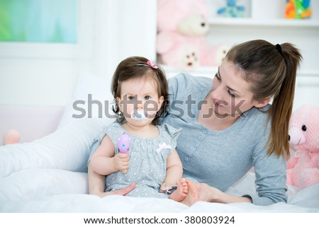 Young mom hugging her baby little girl with pacifier in the mouth on the bed. Baby looking at camera. Shallow doff - stock photo