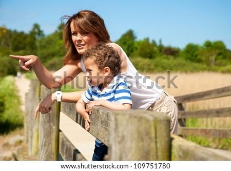 Young mom pointing and explaining something to his little son - stock photo