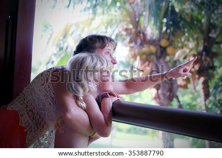 Young mom showing something to her little daughter from the balcony of tropical hotel - stock photo
