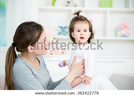 Young mom talking to her baby girl, baby looking away.Baby room interior. Shallow doff - stock photo