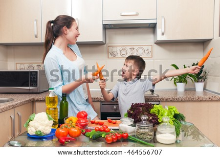 Young Mom with child having fun in the kitchen during the preparation of dietary salad