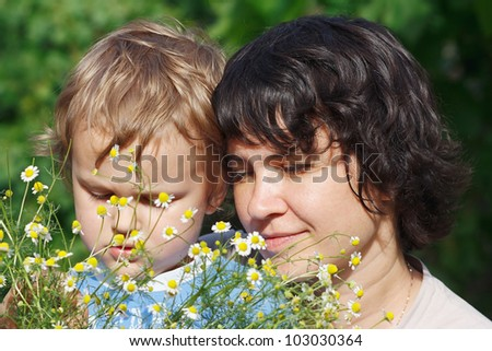 Young mom with her son among the summer daisies outdoors