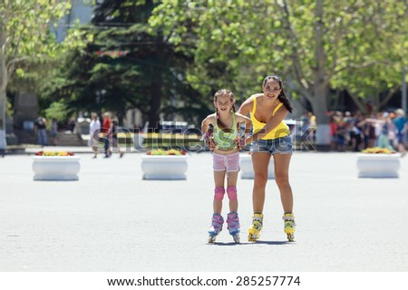 Young mom with her 6 years old child rollerskating in the city street - stock photo
