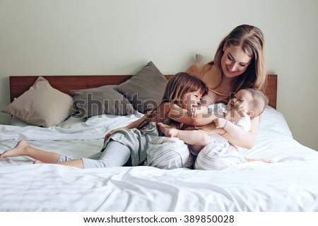 Young mom with her 5 years old daughter and 4 months old baby dressed in pajamas are relaxing and playing in the bed at the weekend together, lazy morning - stock photo