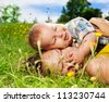 young mommy and her baby laying on the grass and hugging - stock photo