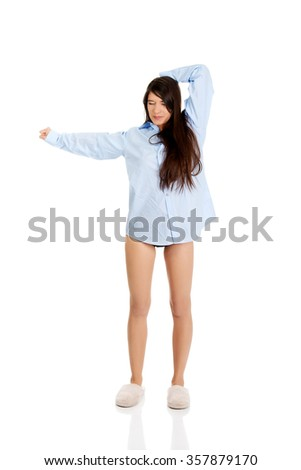 Young morning woman in big shirt and slippers.