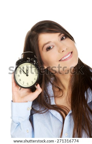 Young morning woman in big shirt holding alarm clock. - stock photo
