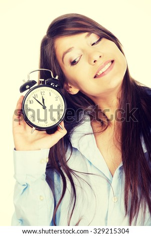 Young morning woman in big shirt holding alarm clock.