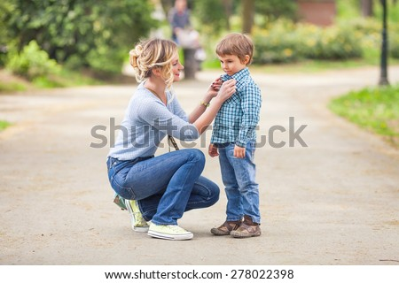 Young mother adjusting son's shirt collar while walking in a park - stock photo