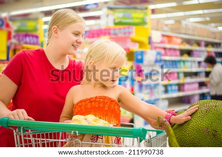 Young mother and adorable girl in shopping cart looks at giant jack fruits on boxes in supermarket