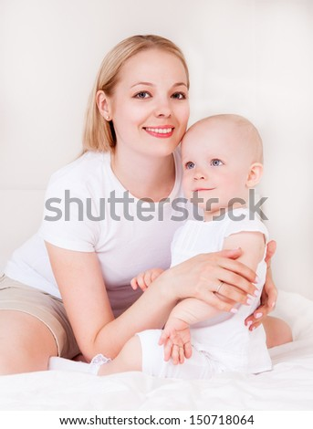 young mother and baby in bed at home
