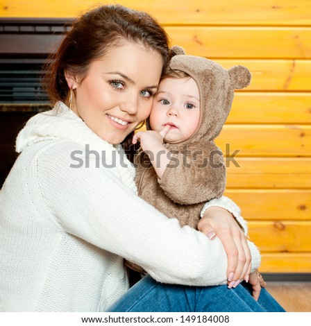 young mother and baby in home interior - stock photo