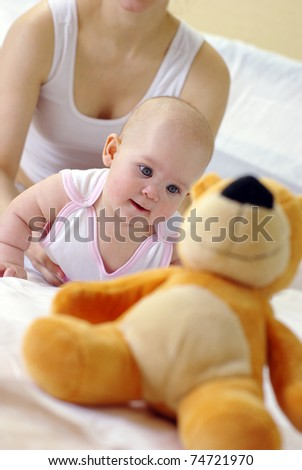 young mother and baby lying on the bed playing with a bear toy - stock photo