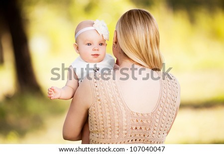 young mother and baby outdoor on a warm summer day
