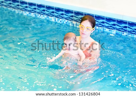 Young mother and baby playing in a swimming pool - stock photo