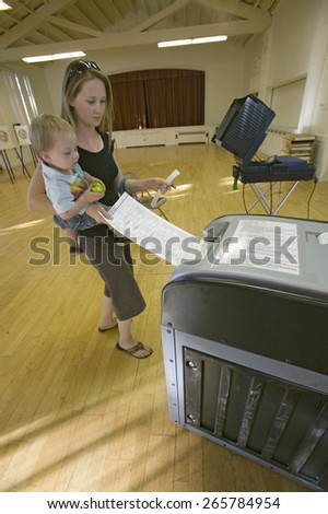 Young mother and Baby (Sophia Larson) inserts completed ballot for Congressional election, November 2006, into an electronic scanner in Ojai, Ventura County, California - stock photo