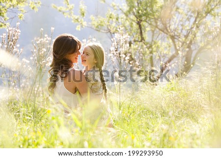 Young mother and child daughter together, hugging and joyfully laughing while relaxing in a golden field of sunshine and spring flowers while on a summer holiday. Family outdoors lifestyle. - stock photo